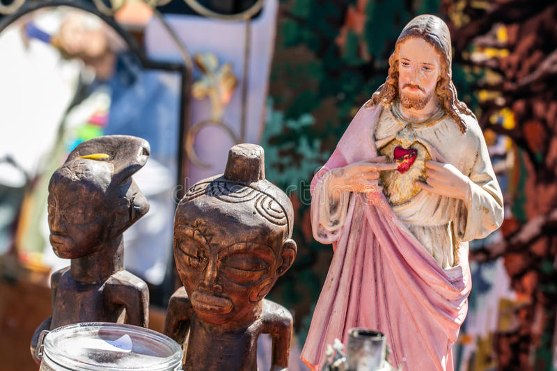 Polytheism religion symbols, Christ and wooden African statues at garage sale. Closeup of various religions and polytheism symbols, Christ and traditional wooden royalty free stock image