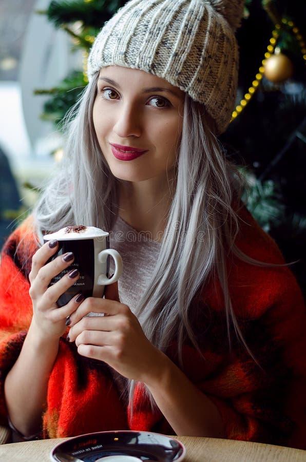 pom pom帽子和红色围巾的美丽的白肤金发的女孩有葡萄酒红嘴唇的喝咖啡的,看照相机 免版税库存照片