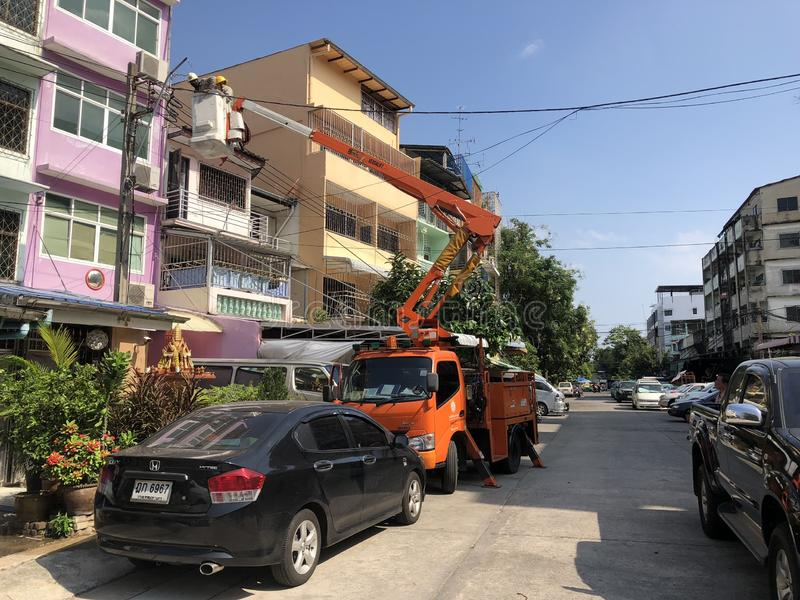 Pom Prap Sattru Phai District, Bangkok, Thailand - 19 March 2018: Electrician on the truck crane shifted up to check and repair stock image