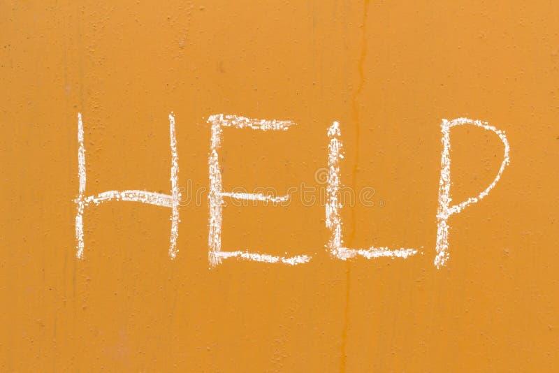 Pomaga handwriting z kredą na pomarańczowym metalu tle obraz royalty free