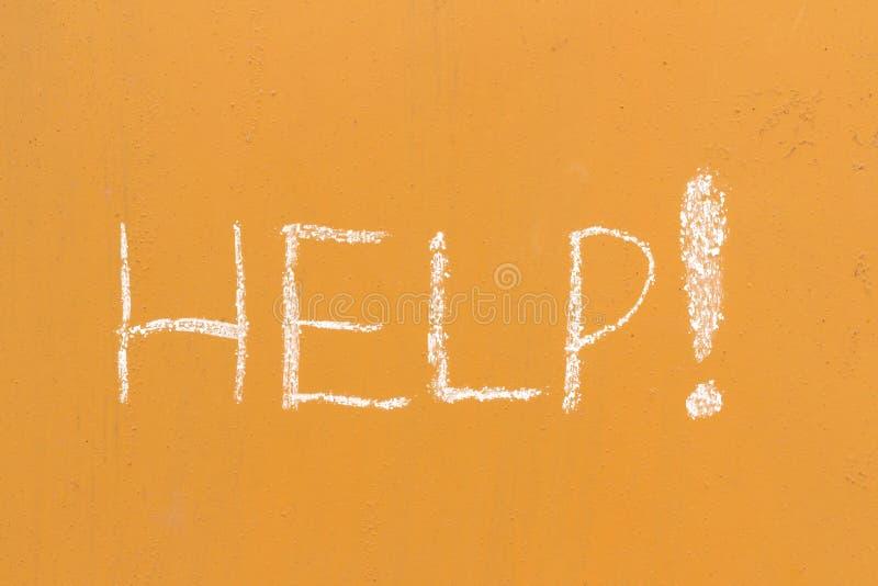 Pomaga handwriting z kredą na pomarańczowym metalu tle fotografia royalty free