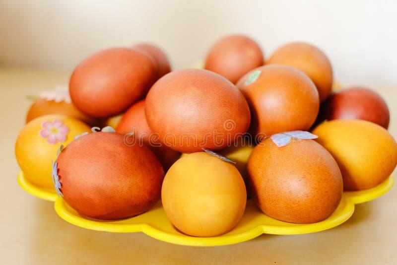 Pomarańczowi Wielkanocni jajka na koloru żółtego talerzu zdjęcie royalty free
