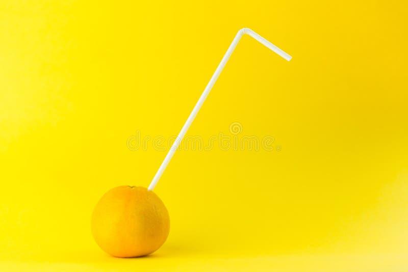 Pomarańcza ze słomą wyizolowaną na pomarańczowym fotografia royalty free