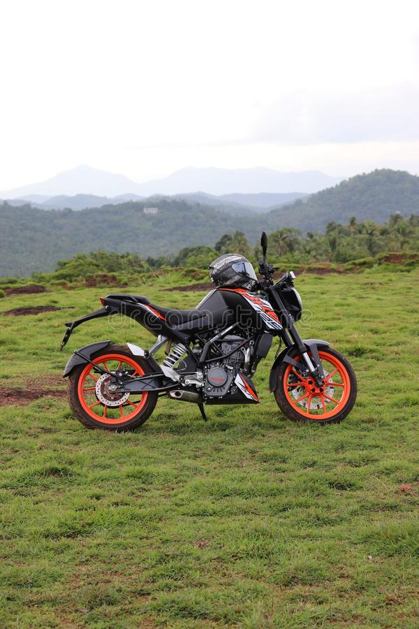 Pomarańcze bawi się motorowego rower odpoczywa na zielonym wzgórzu obrazy stock
