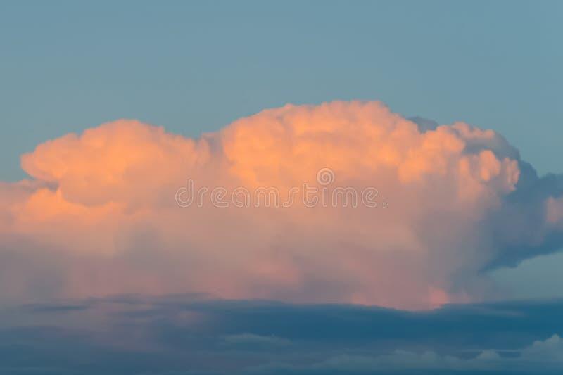 Pomarańcze chmura na niebieskim niebie przy zmierzchem zdjęcie royalty free