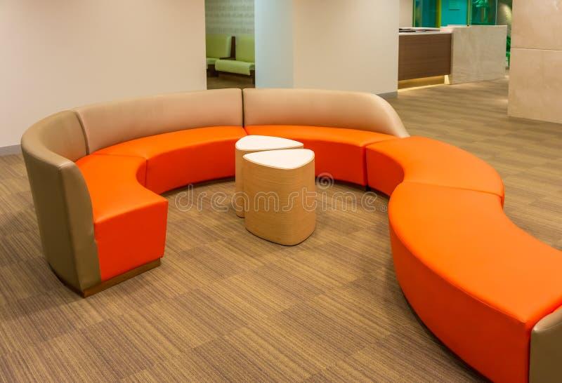 Pomarańcze długa rzemienna kanapa z bocznym drewnianym stołem obraz royalty free