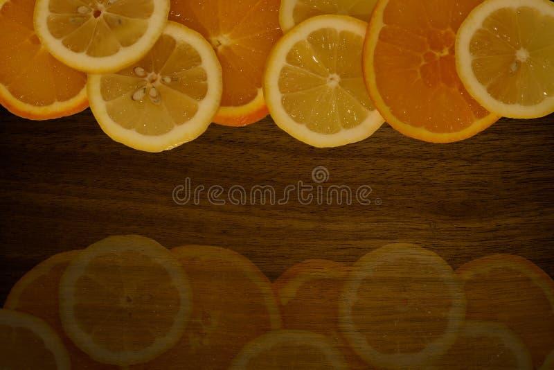 Pomarańcze i cytryna pokrajać na drewnianym stole zdjęcie royalty free
