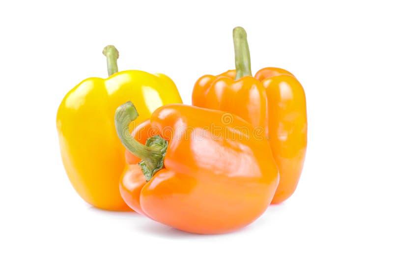 Pomarańcze i kolor żółty pieprzymy na białym tle odosobniony obraz royalty free