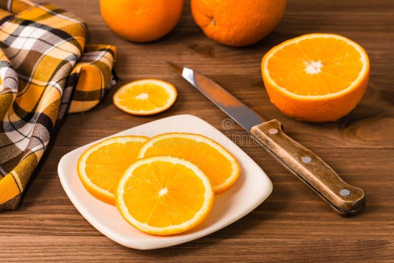 Pomarańcze, nóż, pielucha, i obraz stock