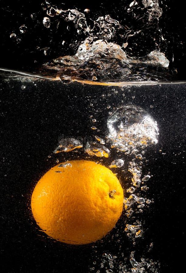 Pomarańcze pod wodą na czarnym tle zdjęcia stock