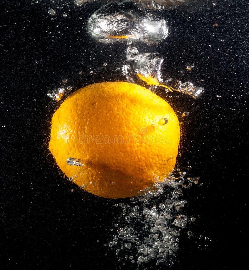 Pomarańcze pod wodą na czarnym tle obrazy stock