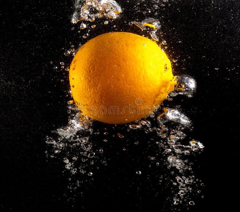 Pomarańcze pod wodą na czarnym tle zdjęcie royalty free