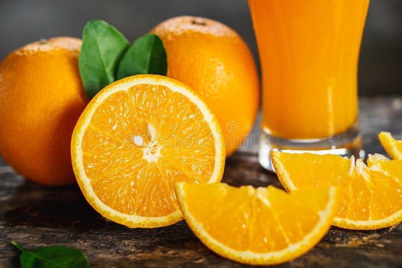 Pomarańcze pokrajać i soków pomarańczowych szkła z zielonym liściem na drewnianym stole obrazy stock