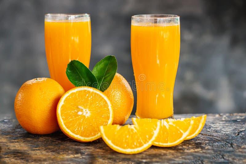 Pomarańcze pokrajać i soków pomarańczowych szkła z zielonym liściem na drewnianym stole obraz royalty free