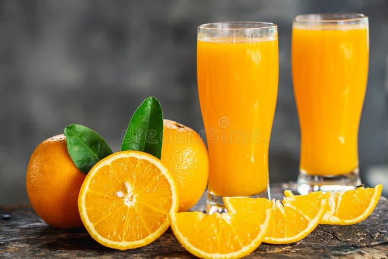 Pomarańcze pokrajać i soków pomarańczowych szkła z zielonym liściem na drewnianym stole obrazy royalty free