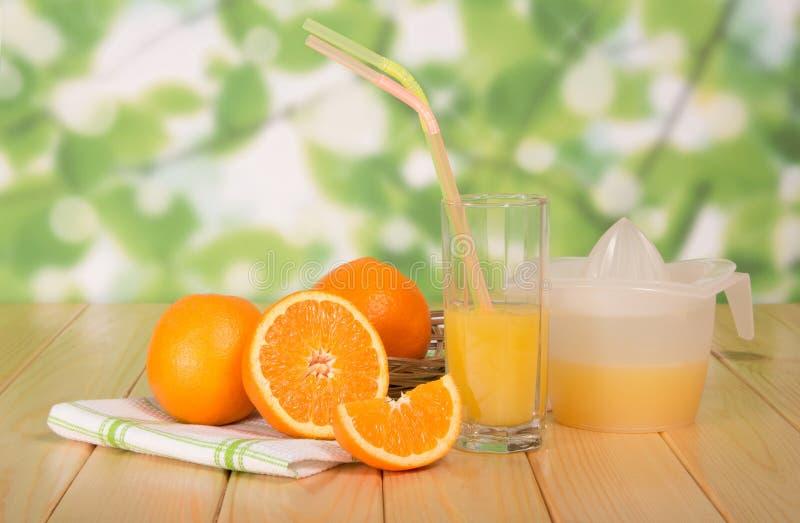 Pomarańcze, szkło sok, prasa na stole obraz stock