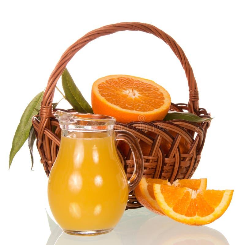Pomarańcze w koszu, dzbanek z sokiem na bielu obraz stock