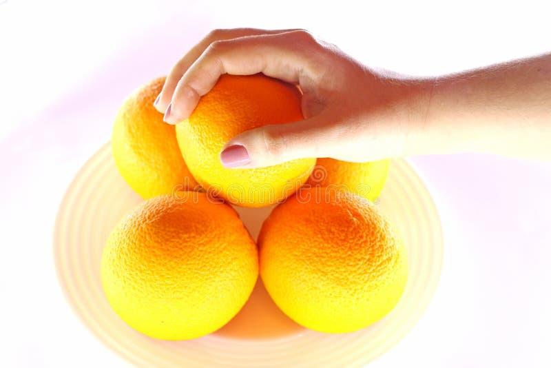 Pomarańcze w pucharze i ręce od above fotografia stock