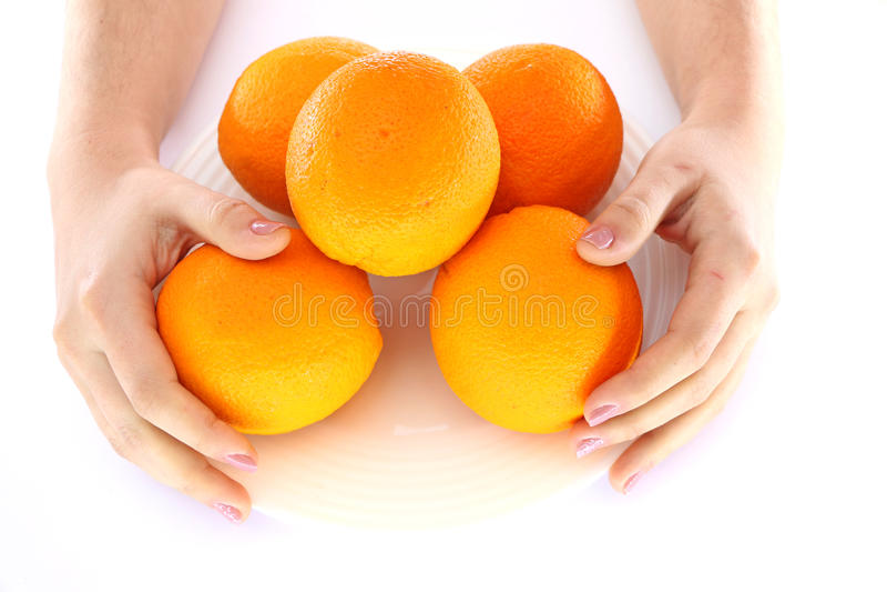 Pomarańcze w pucharze i ręce z one zdjęcie stock