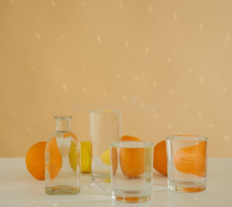 Pomarańcze za szklanymi naczyniami wypełniającymi z wodą Zniekształcający odbicie na beżowym tle zdjęcia royalty free