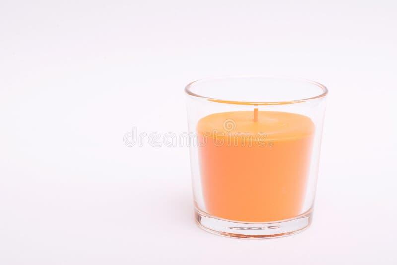 Pomarańczowa świeczka w szkle isolate obrazy stock
