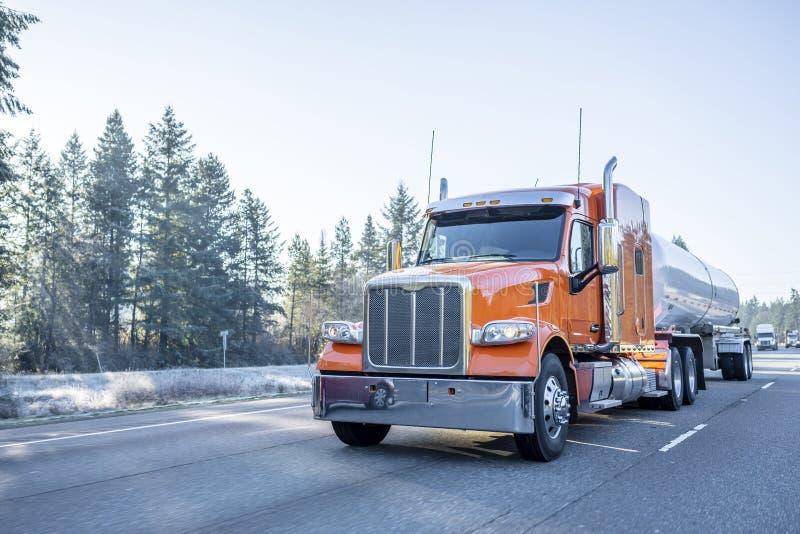 Pomarańczowa duża takielunku semi ciężarówka z długim zbiornika semi przyczepy odtransportowania cieczem i upłynniający chemiczny obraz royalty free