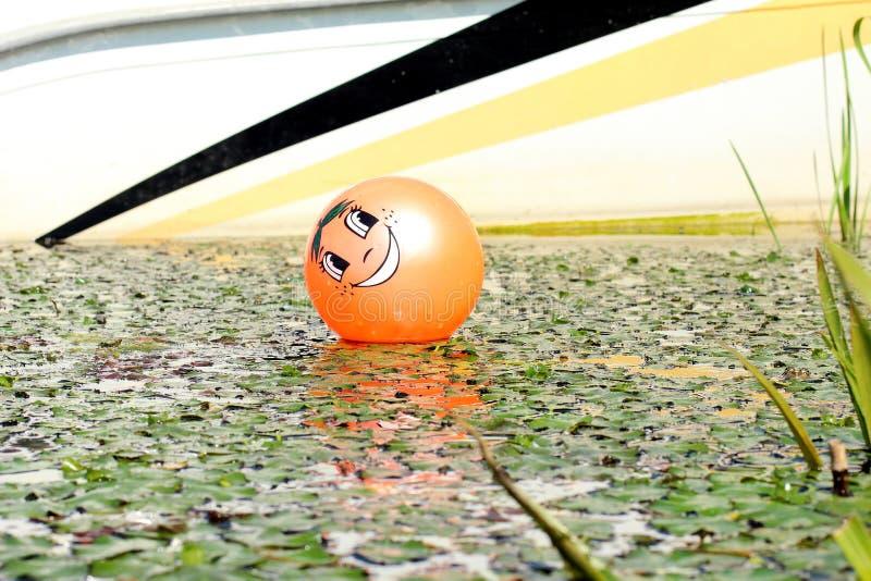 Pomarańczowa helowa piłka z wizerunkiem smiley jest na wodzie z zieloną roślinnością obrazy royalty free
