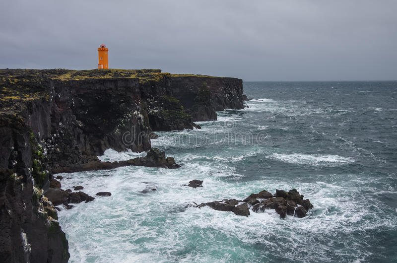 Pomarańczowa latarnia morska na czarnej rockowej falezie zachodni Islandzki fotografia stock