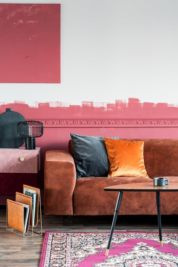 Pomarańczowa poduszka na sofie brązowej w modnym salonie z kommodem i drewnianym stolikiem do kawy obraz stock