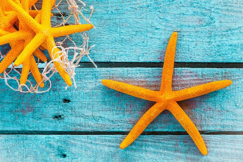 Pomarańczowa rozgwiazda na turkusowych deskach z ryba siecią obraz royalty free