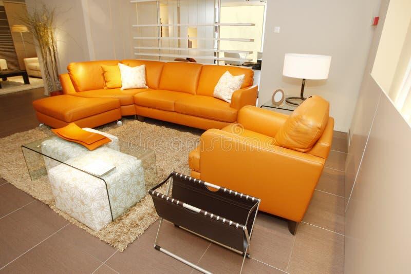 Pomarańczowa rzemienna leżanka i karło ustawiający w meble