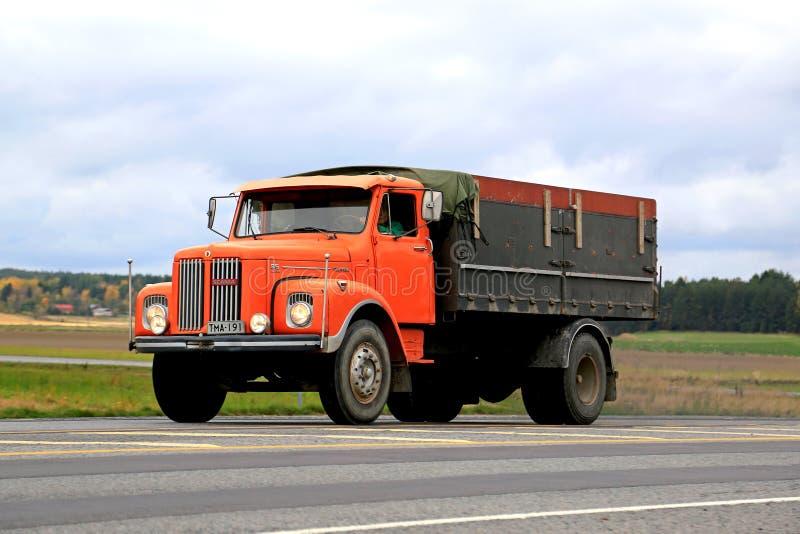 Pomarańczowa Scania L85 Super ciężarówka na drodze obrazy royalty free