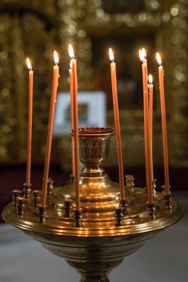 Pomarańczowe świeczki stojaka w żelaznym candlestick i ogieniu zaświecają obraz royalty free