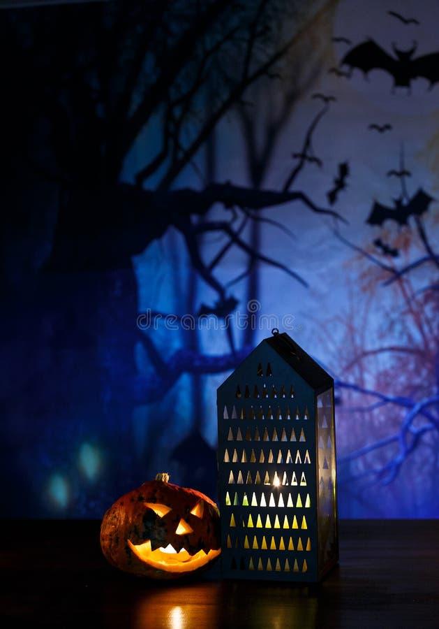 Pomarańczowe banie z strasznymi twarzami, lampionem i świeczkami kłamstw na stole przed zmrokiem, - błękitny tło Halloweenowy ?wi obraz royalty free