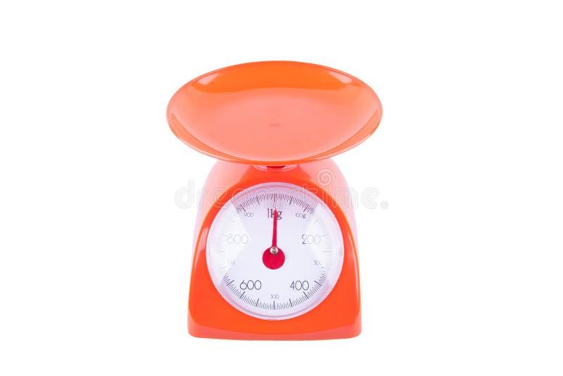 Pomarańczowe ciężar skale na białego tła wyposażenia kuchennym przedmiocie odizolowywającym obraz stock