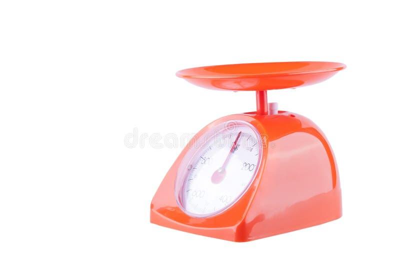 Pomarańczowe kuchenne skale mierzą w kilo na białego tła wyposażenia kuchennym przedmiocie odizolowywającym obrazy royalty free