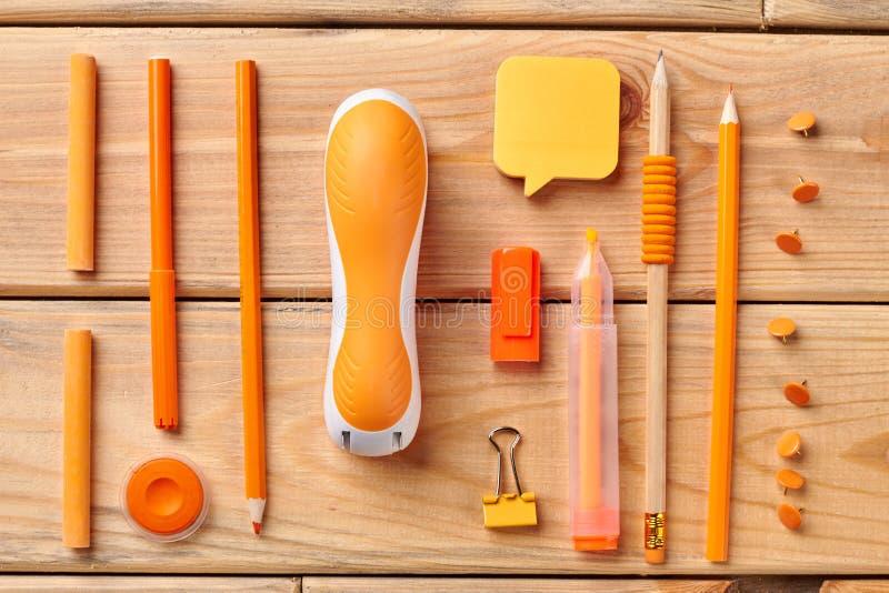 Pomarańczowe materiały dostawy na drewnianym tle obrazy royalty free