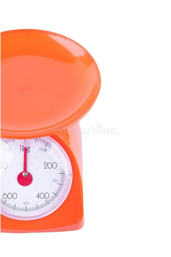 Pomarańczowe skale waży produkty na białego tła wyposażenia kuchennym przedmiocie odizolowywającym fotografia stock