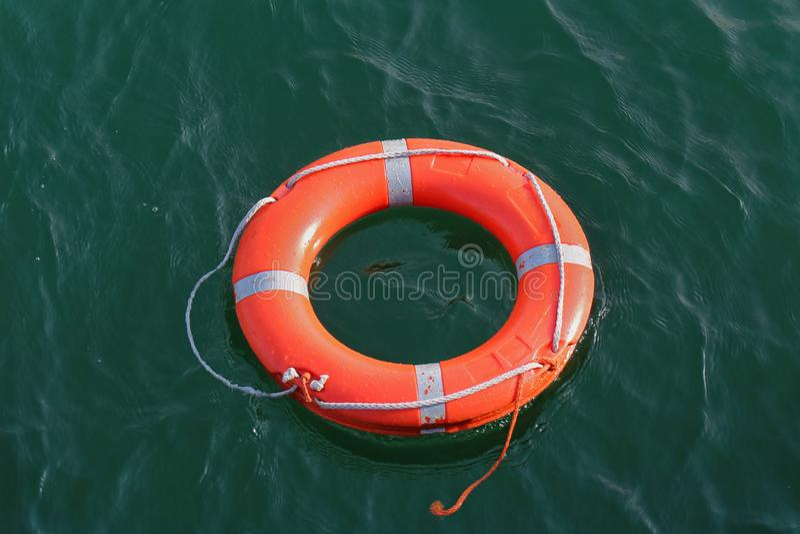 Pomarańczowego okręgu lifebuoy unosić się na wodzie zdjęcie royalty free