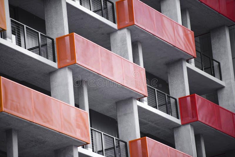 Pomarańczowi i czerwoni balkony na nowożytnym betonowym wieżowu w zdjęcie stock