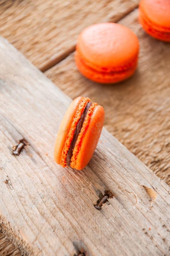 Pomarańczowi macarons z czekoladowym ganache plombowaniem obrazy stock