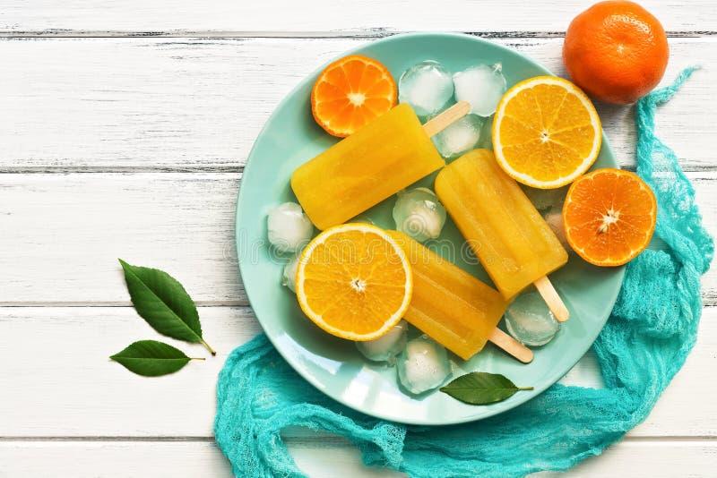 Pomarańczowi Tangerine popsicles w błękita talerzu z kostkami lodu i plasterkami owoc, biały drewniany nieociosany tło Odgórny wi zdjęcie royalty free