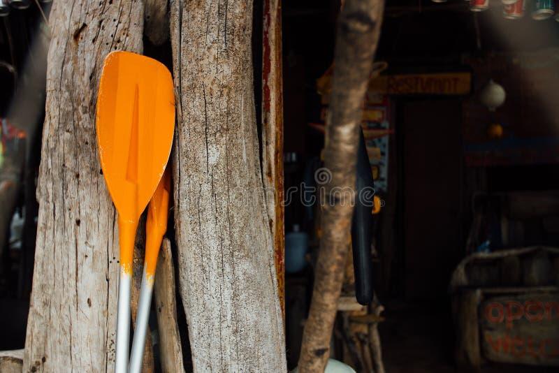 Pomarańczowi wiosła na drewnianym tle Dwa pomarańczowego paddles dla dennej łodzi kajaka lub obraz stock
