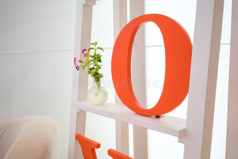 Pomarańczowy abecadło na białej półce z kwiatem fotografia stock
