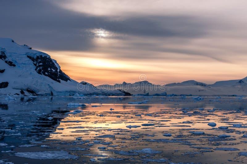 Pomarańczowy biegunowy zmierzch nad górami z lodowami i driftin obrazy stock