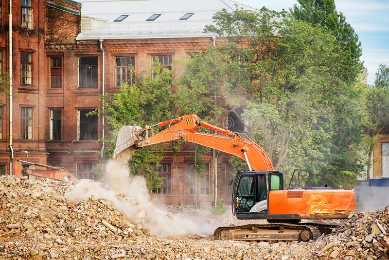 Pomarańczowy ekskawator pracuje na ruinach wyburzający budynek zdjęcia stock