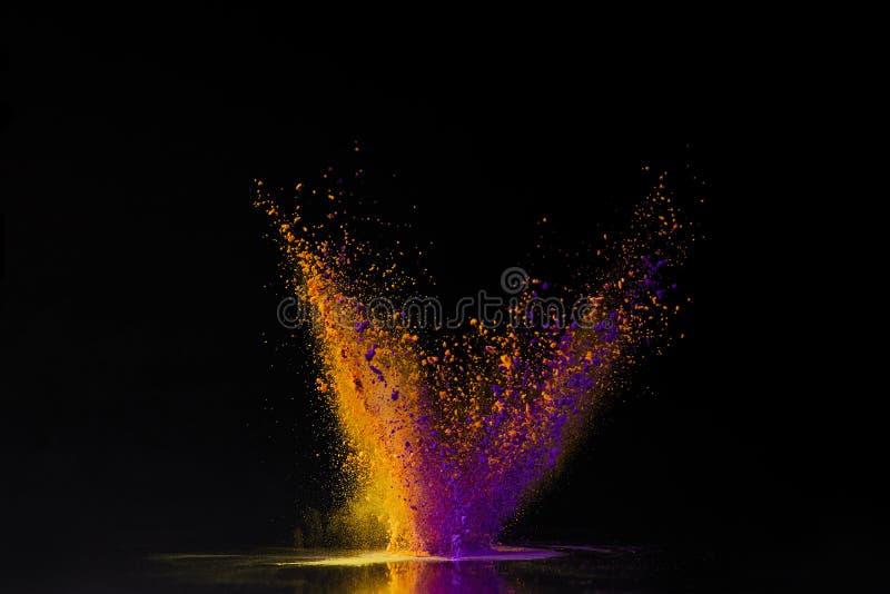 Pomarańczowy i purpurowy holi proszka wybuch na czerni fotografia stock