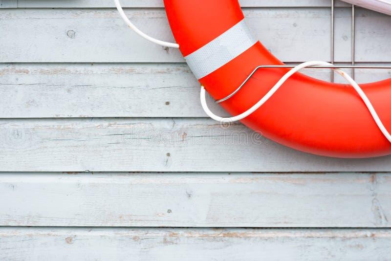 Pomarańczowy lifebuoy na biel ścianie w porcie fotografia royalty free