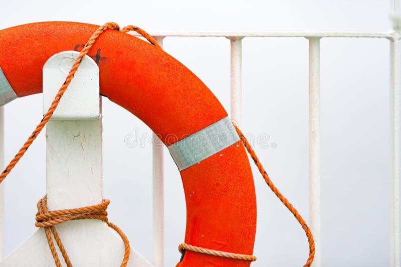 Pomarańczowy lifebuoy na biel ścianie w porcie fotografia stock