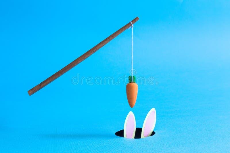 Pomarańczowy marchwiany obwieszenie na kiju nad czarna dziura z królikiem w nim abstrakt odizolowywający na błękicie obraz stock